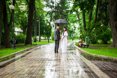Newly married couple walking under umbrella in rain Royalty Free Stock Images