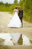 Newly-married couple walks on rural road Royalty Free Stock Photos