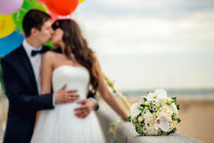 Newly-married couple and wedding bouquet in the Royalty Free Stock Image