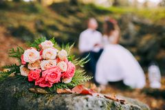 Newly-married couple and wedding bouquet in the foreground. royalty free stock photos