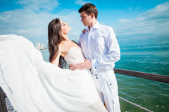 Newly married couple after wedding in luxury resort. Romantic bride and groom relaxing near sea. Honeymoon. Royalty Free Stock Photography