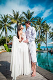 Newly married couple after wedding in luxury resort. Romantic bride and groom relaxing near swimming pool. Honeymoon. Royalty Free Stock Image