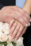 Newly married - hands with gold rings. On a beautifull wedding bouquet Stock Photos