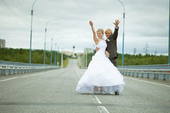 Newly married have fun on highway Stock Images