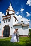 Newly married kiss on a background of church Royalty Free Stock Photo