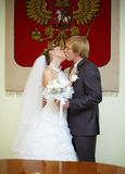Newly married kiss under Russian arms Stock Photo