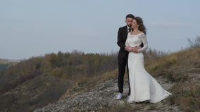 Newly married wedding couple stand near a cliff overlooking the sea. stock video