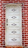 Newly painted white door behind grate on fresh brick wall. In Trinidad, Cuba stock photos