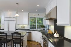 Newly Remodeled White Kitchen. Interior shot of a recently remodeled kitchen featuring white custom cabinets, stainless steel appliances and an oak floor Stock Photo