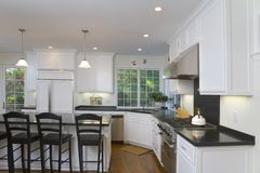 Newly Remodeled White Kitchen. Interior shot of a recently remodeled kitchen featuring white custom cabinets, stainless steel appliances and an oak floor Royalty Free Stock Photos