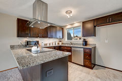 Newly renovated kitchen with dark wood cabinets and granite coun Royalty Free Stock Image