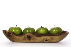 Newly washed green apples in olive wood bowl. Line of four newly-washed organic green apples in a narrow carved olive wood bowl stock photography