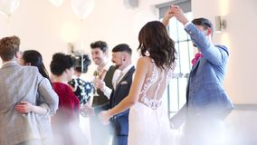 First Dance At Our Wedding. Newly wed couple are dancing together at their wedding with all of their guests stock video footage
