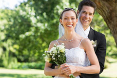 Newly wed couple with flower bouquet in park Royalty Free Stock Photo
