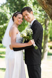 Newly wed couple with head to head in garden Royalty Free Stock Photos
