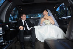 Newly wed couple in limousine Stock Photography