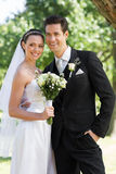 Newly wed couple looking away in park Stock Image