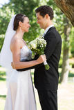 Newly wed couple looking at each other in garden Royalty Free Stock Photography