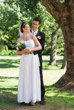 Newly wed couple looking at each other in park Stock Images