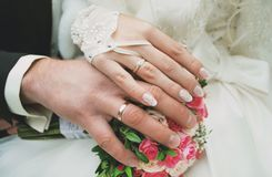 Newly wed couple`s hands with wedding rings. On a bouquet of roses. Gloves are on the bride`s hand Stock Images