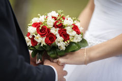 Newly wed couple's hands with wedding rings. Hands of bride and groom with rings on wedding bouquet Stock Photo