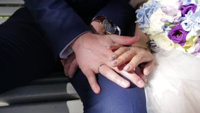 Newly wed couple`s hands with wedding rings. Bride and groom with wedding rings on flowers or wedding bouquet. Newly wed. Couple`s hands with wedding rings HD stock footage