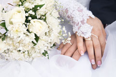Newly wed couple`s hands with wedding rings. Hands of the groom and the bride on a wedding bouquet from roses of white color Royalty Free Stock Photo