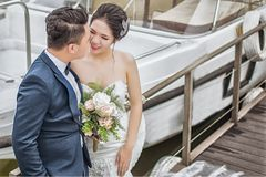 Newly Wed Couple Standing on Brown Wooden Dock Near Boat stock image