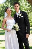 Newly wed couple standing in garden Stock Photo