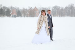 Newly wed couple standing in winter field Stock Image