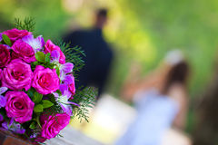 Newly wed couple walking away from bridal bouquet stock photos