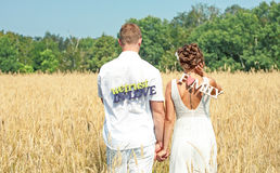 Newly wed couple walking through a grassland. Happy bride and groom walking in a field Stock Images