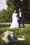 Newly wed holding hands, wedding bouquet in the foreground Royalty Free Stock Image