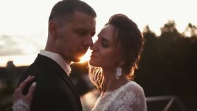Newly wed loving couple hugs and kisses on the sunset stock video