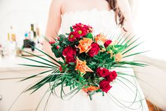 Newly Wed Woman Holding her Red, Orange and Green Bridal Bouquet royalty free stock image