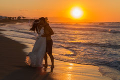 Newly wed young couple on a hazy beach at dusk Stock Photo
