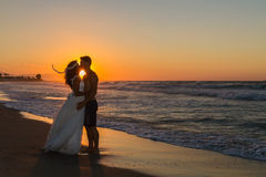 Newly wed young couple on a hazy beach at dusk Royalty Free Stock Images