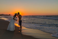 Newly wed young couple on a hazy beach at dusk Stock Image