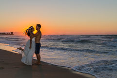 Newly wed young couple on a hazy beach at dusk Stock Photos