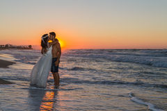 Newly wed young couple on a hazy beach at dusk Royalty Free Stock Photo