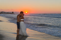 Newly wed young couple on a hazy beach at dusk Stock Photos
