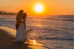 Newly wed young couple on a hazy beach at dusk Royalty Free Stock Photos