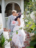 Newly wedded couple in the park. Just married in day of them wedding. Groom kisses his bride stock photo