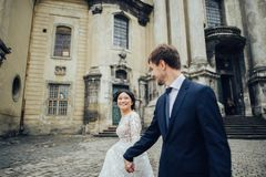 Newly wedded couple posing near antique green door stock images