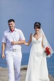 Newly wedded couple on seafront Stock Photo