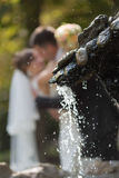 Newly wedded kissing behind fountain Royalty Free Stock Photos