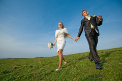 Newly wedded running along the field Royalty Free Stock Photography