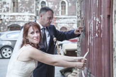 Newly wedding couple trying to open doors Stock Image
