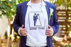 Newlywed in blue costume with opened shirt showing t-shirt with royalty free stock photo