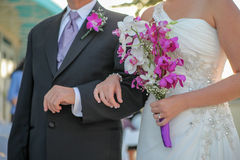Newlywed bride and groom. Bodies of newlywed bride and groom with bouquet linking arms Royalty Free Stock Photos